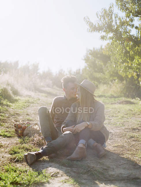 Couple sitting on a sunlit path — Stock Photo