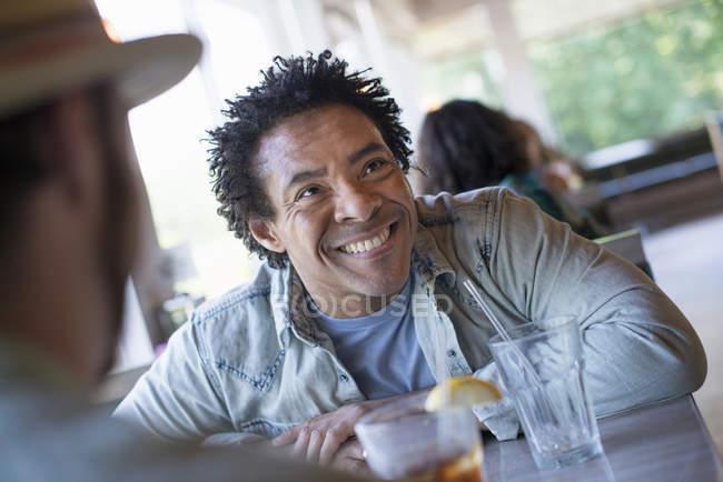 Человек, сидя в закусочной, глядя вверх — стоковое фото