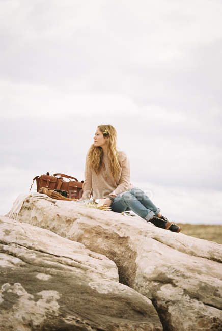 Woman sitting on a rock — Stock Photo
