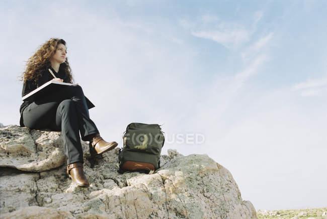 Donna seduta su una roccia con blocco note — Foto stock