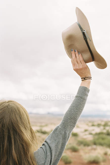 Mujer sostiene un sombrero - foto de stock
