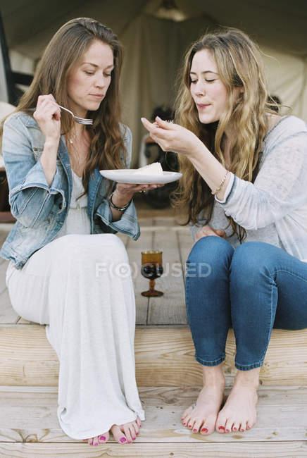 Mulheres, partilha de bolo e um copo de vinho — Fotografia de Stock