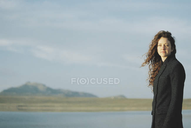 Woman standing on the shore of a lake. — Stock Photo