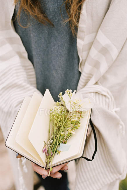 Woman holding a notebook with wild flowers — Stock Photo