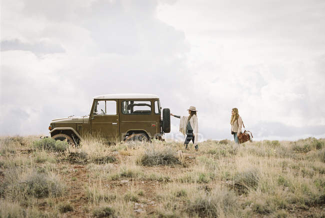 Women by a jeep in open space — Stock Photo
