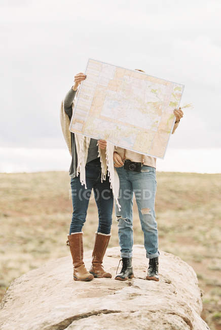 Women holding up a large map — Stock Photo