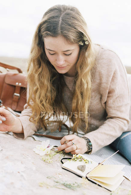 Woman putting wild flowers between the pages — Stock Photo