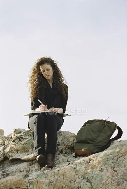 Woman sitting on a rock, writing in a notebook — Stock Photo