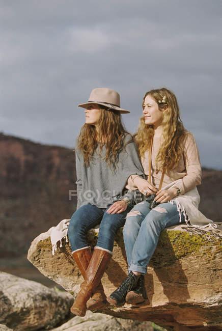 Boho-Frauen sitzen auf einem Felsen in der Wüste — Stockfoto