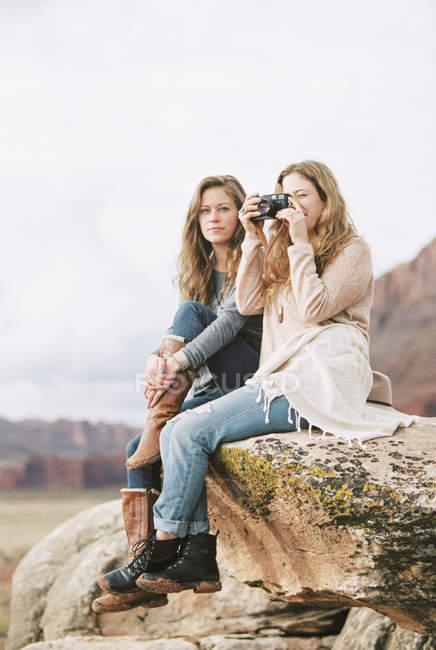 Mulheres sentadas numa rocha num deserto — Fotografia de Stock