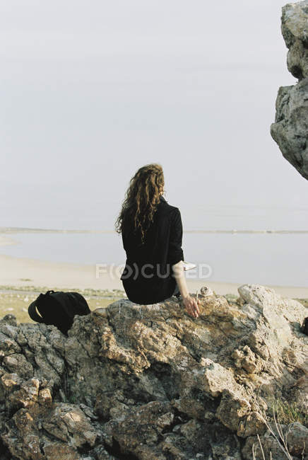 Kayanın üzerinde oturan kadın - foto de stock
