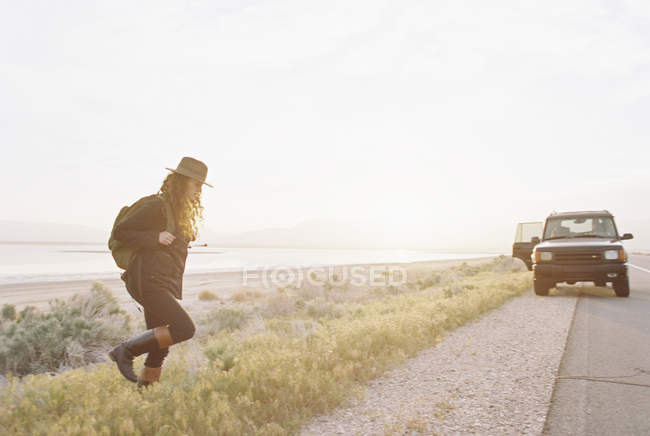Donna che indossa un cappello e cammina verso una jeep — Foto stock