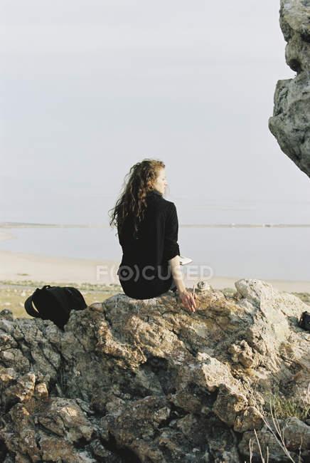 Mujer sentada en una roca mirando - foto de stock