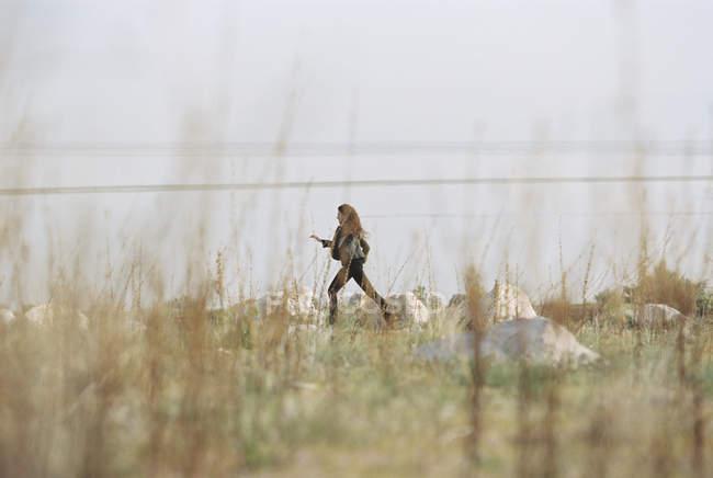 Donna che cammina attraverso l'erba — Foto stock