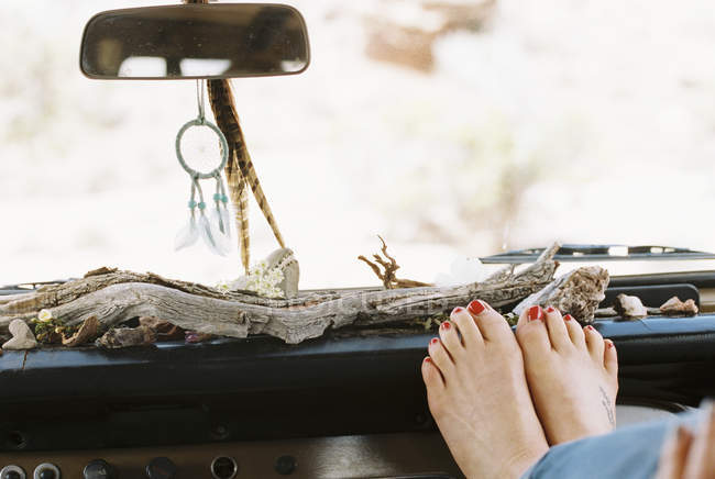 Barefoot woman resting feet on the dashboard — Stock Photo
