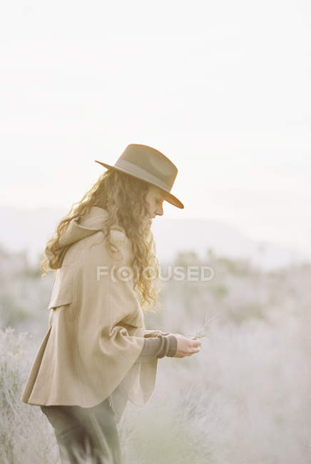 Donna in cappello raccogliendo fiori selvatici — Foto stock