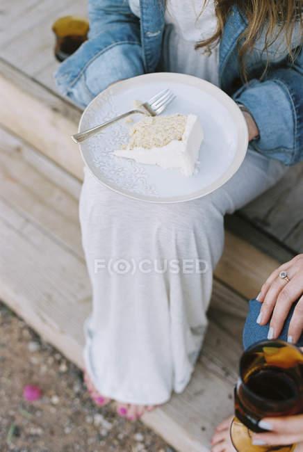 Piatto con una fetta di torta sul ginocchio della donna . — Foto stock