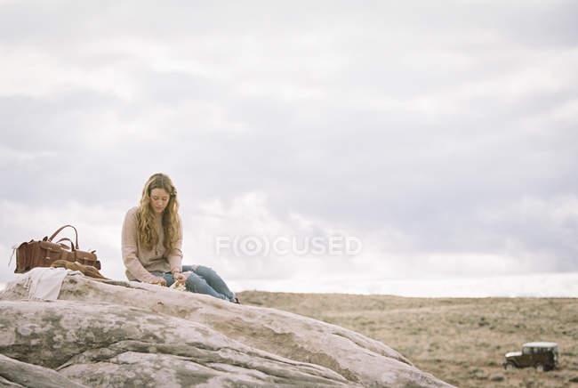 Frau sitzt auf einem Felsen — Stockfoto