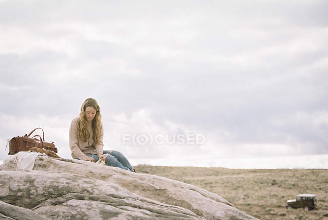 Женщина сидит на камне — стоковое фото