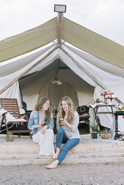Women sitting outside a large tent — Stock Photo