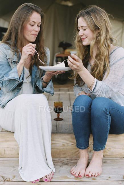 Frauen teilen Kuchen und ein Glas Wein. — Stockfoto