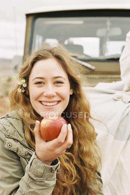 Женщина, протягивающая красное яблоко — стоковое фото