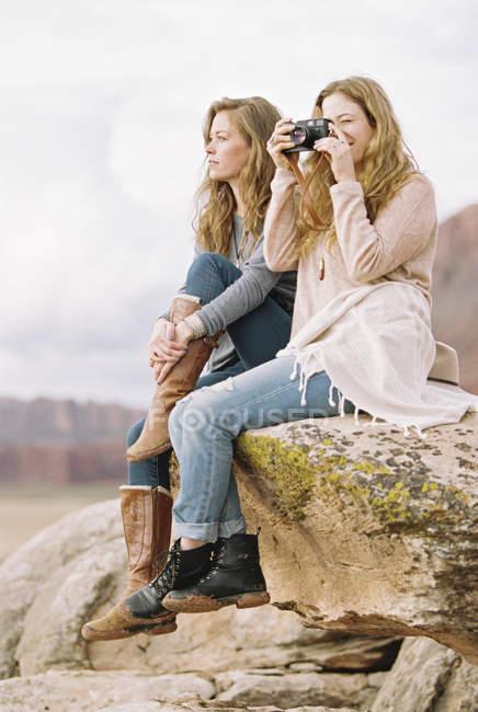 Женщины, сидящие на скале в пустыне — стоковое фото