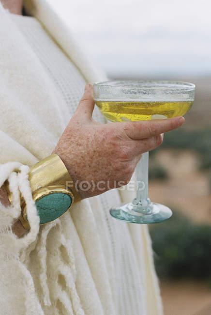 Женщина с золотым браслетом, держащая стакан . — стоковое фото
