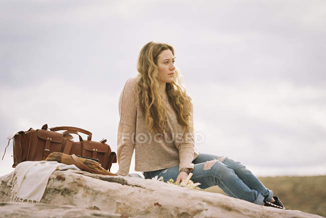 Donna seduta su una roccia — Foto stock