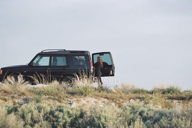 Donna in piedi accanto alla jeep — Foto stock