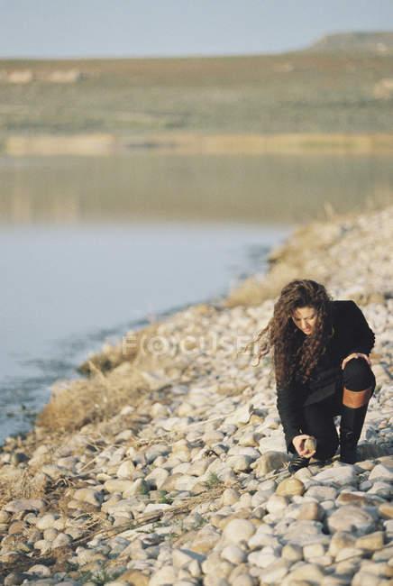 Donna che raccoglie ciottoli — Foto stock