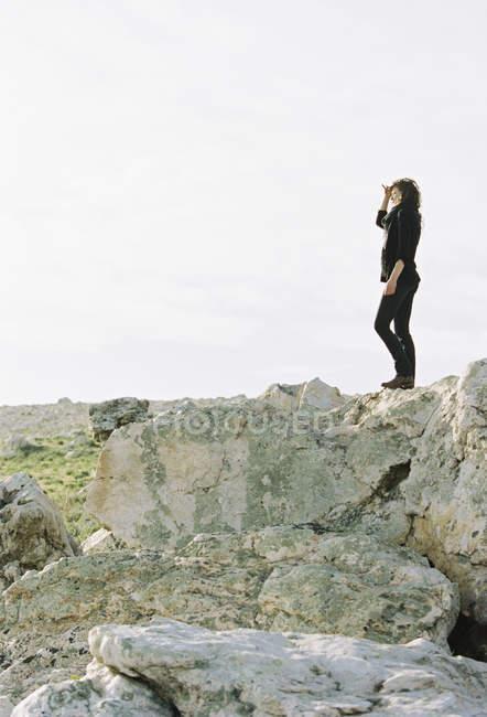 Mulher de pé sobre uma rocha — Fotografia de Stock