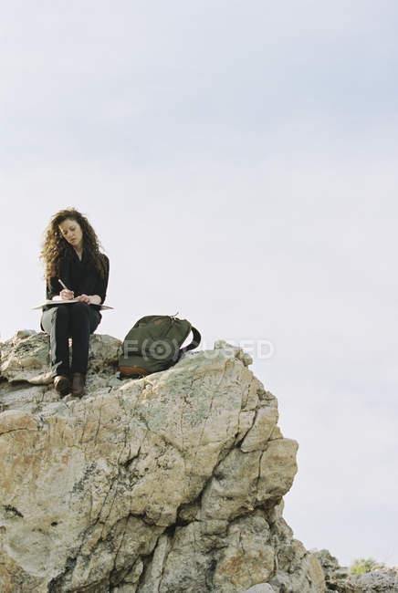 Mujer sentada en una roca, escribiendo en un cuaderno - foto de stock