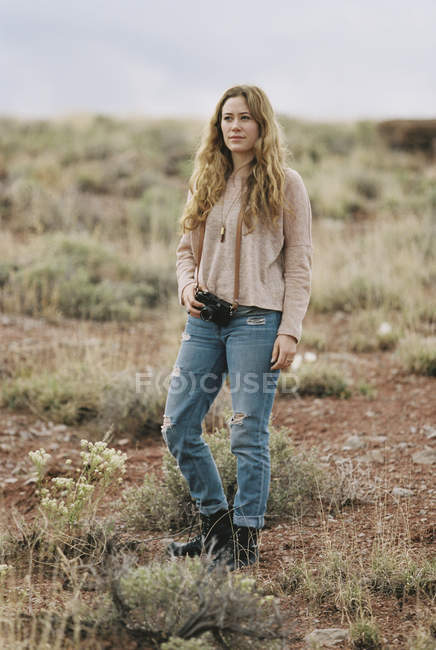 Woman standing holding a camera — Stock Photo