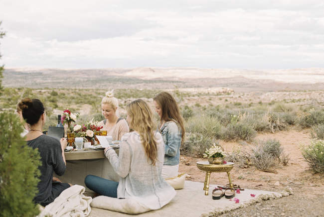 Friends having a meal in Desert — Stock Photo