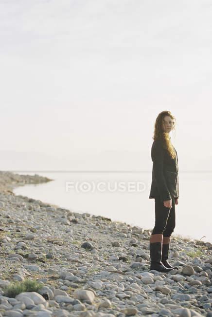Donna in piedi sulla riva di un lago . — Foto stock