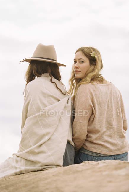 Женщины, сидящие бок о бок на скале — стоковое фото