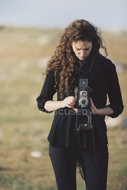 Woman taking a picture with an old camera. — Stock Photo
