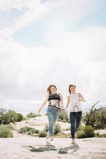Boho women running in desert — Stock Photo