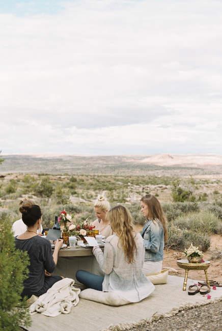 Friends having a meal in Desert — Stock Photo