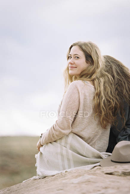 Donne sedute su una roccia in un deserto — Foto stock