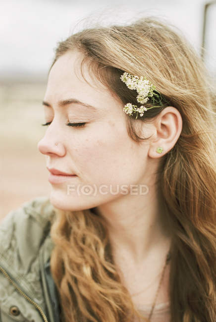 Woman with eyes closed with flowers in hair — Stock Photo