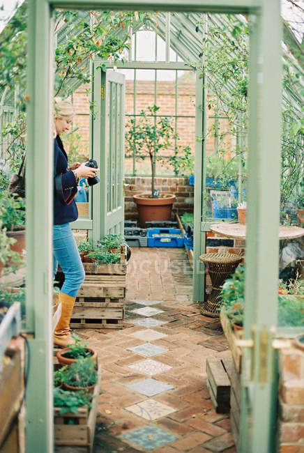 Woman in a conservatory, surrounded by plants. — Stock Photo