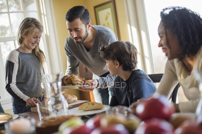 Adults and children gathered around a table — Stock Photo