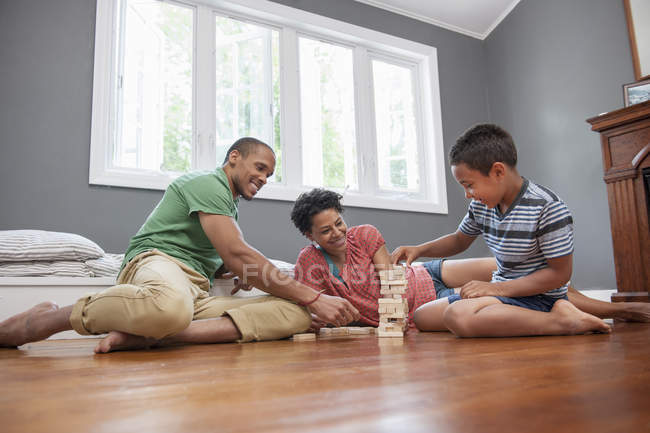 Family on the floor playing a game — Stock Photo