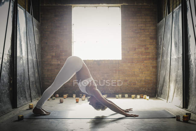 Woman doing yoga surrounded by candles — Stock Photo