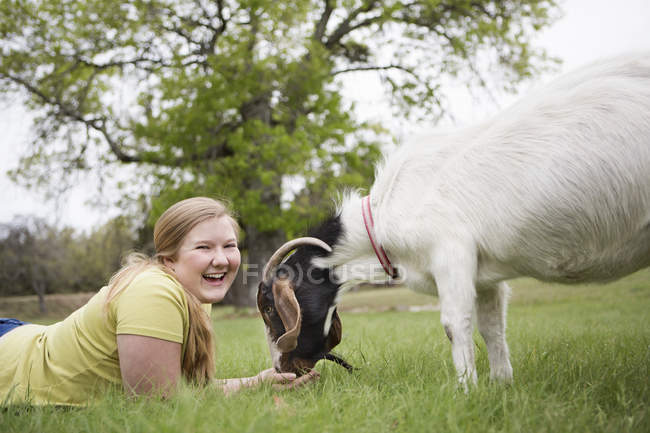 Girl lying on grass with goat — Stock Photo