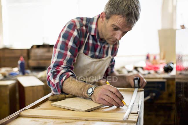 Antique furniture restorer measuring wood — Stock Photo