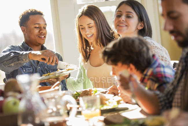 Adults and children, seated around a table — Stock Photo