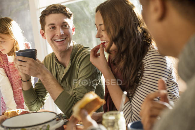 People at table, smiling, eating, drinking — Stock Photo